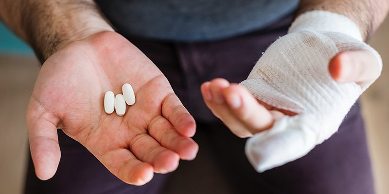 person with bandaged hand and pills